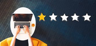 One Star Rating with person using a laptop. On a white table royalty free stock photo