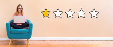 One star rating with woman using a laptop. One star rating with young woman using her laptop in a chair stock photo