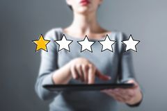 One star rating with woman using a tablet. One star rating with business woman using a tablet computer royalty free stock image