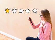 One Star Rating with woman using a tablet. One Star Rating with young woman using her tablet computer stock photo