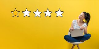 One star rating with woman using a laptop. One star rating with young woman using a laptop computer stock photography