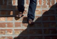 One step ahead - Unique stock photo. Human active legs body parts wearing stylish jeans pant and leather made slippers stock photograph Royalty Free Stock Image