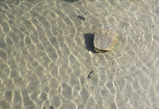 One stone just under the water surface Royalty Free Stock Images