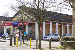 One Stop shop at Two Mile Ash area in Milton Keynes, England. MILTON KEYNES, ENGLAND - MARCH 03, 2015: Sunny view at local supermarket One Stop and people near Royalty Free Stock Photography