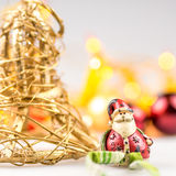 One straw christmas bell and one ceramic santa claus Stock Photos