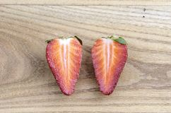 One strawberry cut in half over wood. Royalty Free Stock Photography