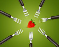 One strawberry between set of forks Royalty Free Stock Images