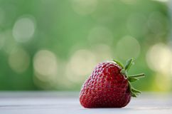 One strawberry on a wooden table Stock Photos