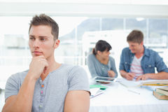 One student standing and thinking as his friends work behind him Stock Image