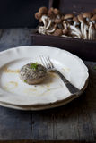 One stuffed mushroom on plate on rustic wooden table with raw mushrooms Royalty Free Stock Photography