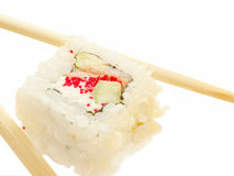 One sushi roll with chopsticks over white Royalty Free Stock Images