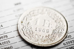 One Swiss Franc coin on fluctuating graph. Stock Image