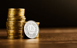 One swiss frank coin and gold money Royalty Free Stock Photography