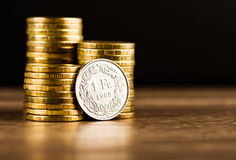 One swiss frank coin and gold money on the desk Royalty Free Stock Photos