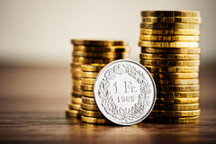 One swiss frank coin and gold money on the desk Stock Photos