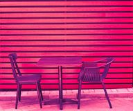 One table and two chairs from wooden boards stand on the street in city s cafe in summer royalty free stock images