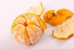 One Tangerine and other peeled. Fresh one tangerine fruit on white background Stock Photography