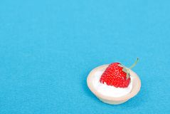 One tartlet with cream and strawberry on a blue background, top Royalty Free Stock Image
