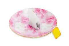 One tea bag on a pink saucer Royalty Free Stock Photos