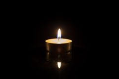One tea candle with reflection on black Stock Photos