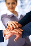 One Team. A group of business people making a pile of hands with a woman at the background Royalty Free Stock Images