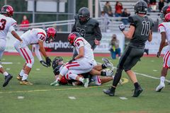 High School Football Tackle. One team tackles players from another team in a game of high school football royalty free stock images