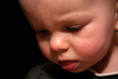 One Tear. Crying baby with one tear royalty free stock photography