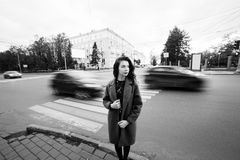 One teenage girl blue coat standing at the traffic light on city street on a cloudly autumn day with vehicles passing by Stock Photos