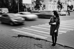 One teenage girl blue coat standing at the traffic light on city street on a cloudly autumn day with vehicles passing by Royalty Free Stock Photo