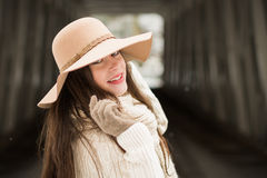 One teenage high school senior portrait wearing floppy hat at covered bridge in winter Royalty Free Stock Images
