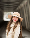 One teenage high school senior portrait wearing floppy hat at covered bridge in winter Stock Images