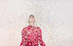 One teenager boy, smiling, looking up, looking above, white back. Ground, studio portrait, red shirt, upper body shot, confetti party Royalty Free Stock Photo