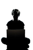 One  teenager silhouette computer computing lap. One caucasian young teenager silhouette boy or girl computer computing laptop full length in studio cut out Stock Photo