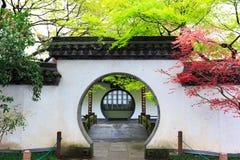 One of the ten scenes of west lake in hangzhou, zhejiang. Suzhou garden style door wall with red green branches stock photos