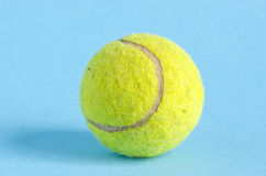 One tennis ball on azure background Stock Image