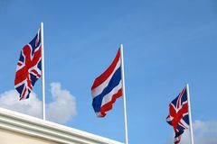One of Thai flag and two Union Jack flag on bright blue sky background. Blown away by wind. Two United Kingdom flag and one Thailand flag with three color, red stock images