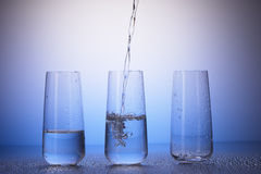 One-third full, half-filled, empty drinking glasses, water Royalty Free Stock Images