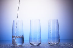 One-third full, two empty drinking glasses. Water pouring royalty free stock photos