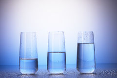 One-third, half-filled and two-thirds full drinking glasses. One-third full, half-filled and two-thirds full drinking glasses with reflection in drops of water royalty free stock image