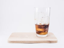 One of thirds soft drink is cool. With two of thirds ice cubes in glass on wood squares royalty free stock images