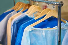 Disposable medical surgical gowns. One-time medical surgical gowns on hangers Stock Photography