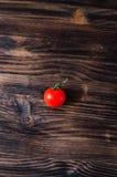 One tomato on old black wood table. One tomato on old black wood background Royalty Free Stock Image