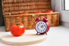 One tomato and red clock. On retro box background royalty free stock photo