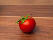 One tomato on wooden table Royalty Free Stock Images