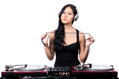 One tough DJ. A young female Asian DJ stretching out the cord from her headphones and making a mean face Stock Photo