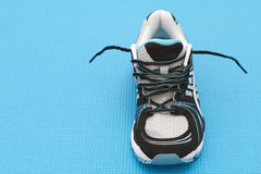 One trainer on blue background. Single training shoe on a blue yoga mat Royalty Free Stock Images