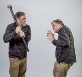 One twin senior about to strike the other with his cane Stock Photography