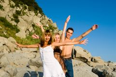 One and two. Girls and the young man wave hands Royalty Free Stock Image
