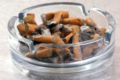 One unhealthy cigarette in an ashtray Royalty Free Stock Images