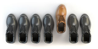 One unique brown boot in the row of black boots. Marketing conce Stock Photo